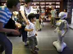 A family tries to talk to SoftBank Corp.'s new companion robot Pepper at a store in Tokyo.