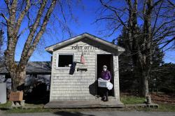 In this Wednesday, May 6, 2020, photo, Postmistress Donna DeWitt carries mail at the tiny post office on Isle Au Haut, Maine