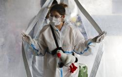 A woman in protective suit passes by a disinfection tent before she enters the departure area of Manila's International Airport.