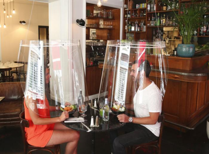 A man and a woman demonstrate dining under a plastic shield in Paris.