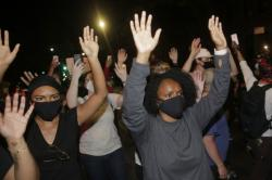Protesters hold their hands in the air in the Brooklyn borough of New York, Saturday, May 30, 2020