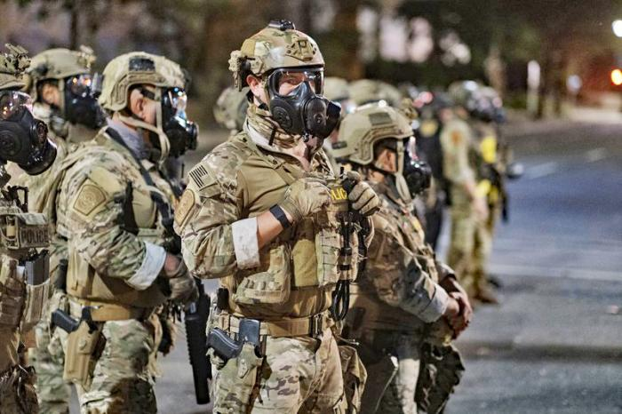 In this photo provided by Doug Brown, agents from different components of the Department of Homeland Security are deployed to protect a federal courthouse in Portland, Ore., Sunday, July 5, 2020