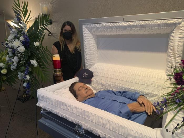 In this July 2020 photo provided by the family, Kristin Urquiza stands next to her father, Mark, during his funeral in Phoenix