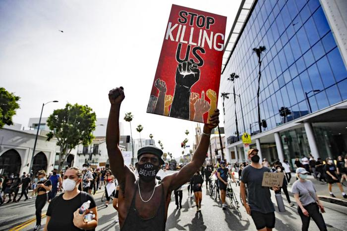 In this June 1, 2020, file photo, a protester carries a sign in the Hollywood area of Los Angeles during demonstrations over the death of George Floyd