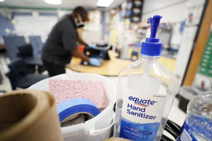 A bottle of hand sanitizer sits on a cart as Des Moines Public Schools custodian Tracy Harris cleans a chair in a classroom at Brubaker Elementary School, Wednesday, July 8, 2020, in Des Moines, Iowa