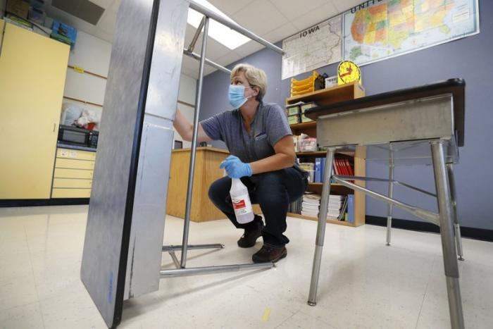 Des Moines Public Schools custodian Cynthia Adams cleans a desk in a classroom at Brubaker Elementary School, Wednesday, July 8, 2020, in Des Moines, Iowa