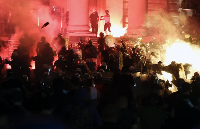 Protesters clash with riot police on the steps of the Serbian parliament during a protest in Belgrade, Serbia, Friday, July 10 2020