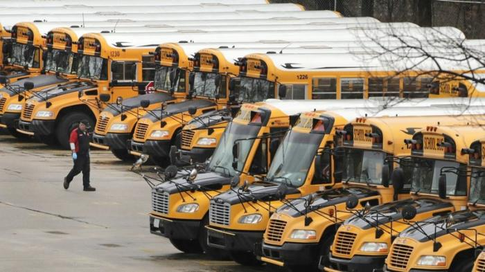 In this April 27, 2020, file photo, a worker passes public school buses parked at a depot in Manchester, N.H.