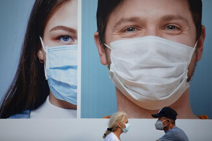 People wearing protective face masks walk by a billboard raising the awareness of wearing face masks and washing hands following government measures to help stop the spread of the coronavirus, in Ramat Gan, near Tel Aviv, Israel, Thursday, July 16, 2020