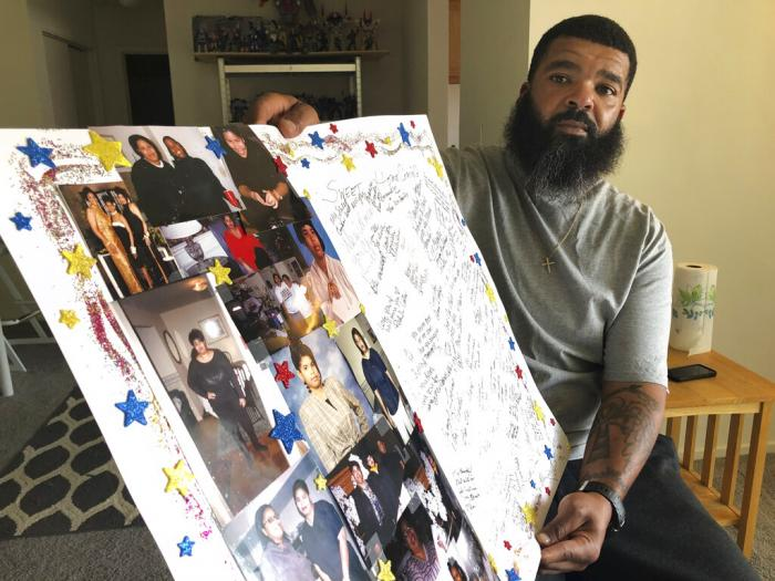 Roland Mack holds a poster with pictures and messages made by family members in memory of his sister, Chantee Mack.
