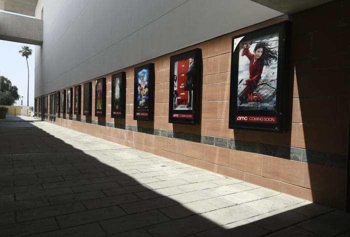 Posters for upcoming movies are displayed in an empty corridor at the currently closed AMC Burbank Town Center 8 movie theaters complex .