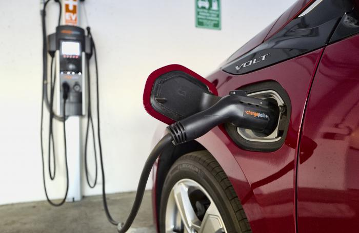 This Oct. 17, 2018 photo shows a Chevrolet Volt hybrid car charging at a ChargePoint charging station at a parking garage in Los Angeles
