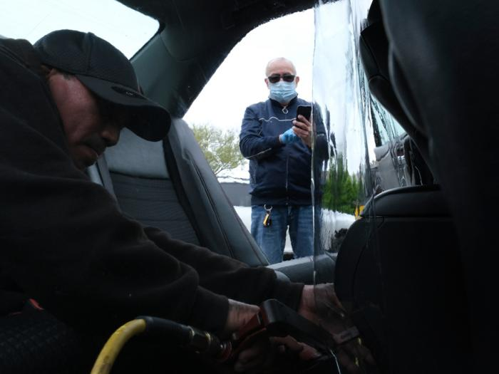 In this May 6, 2020, file photo, Luis Hidalgo, wearing face mask, watches as Joel Rios installs a plastic barrier in his car to protect himself and his passengers from the new coronavirus in the Bronx borough of New York