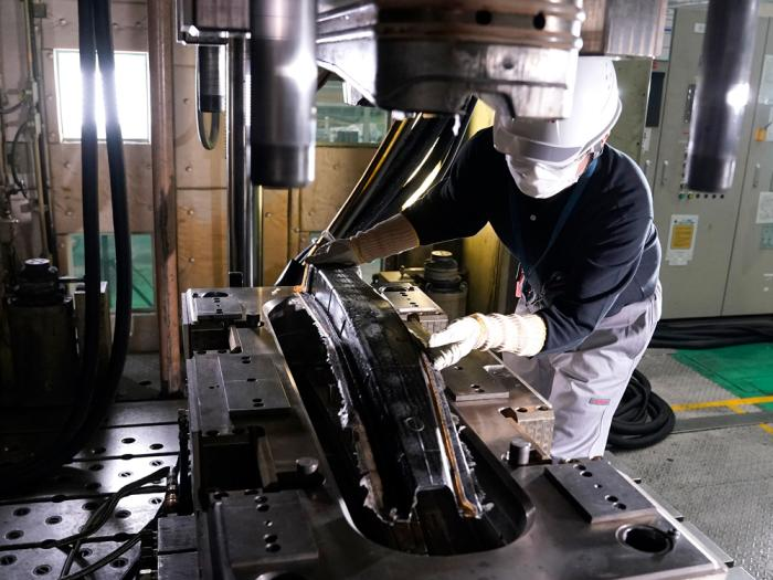 In this image provided by Nissan Motor Co., Lt., an employee works car parts made from carbon fiber reinforced plastics, or CFRP at the Nissan Technical Center in Atsugi, near Tokyo on July 6, 2020