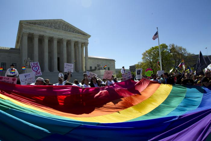 Demonstrators stand in front of a rainbow flag of the Supreme Court in Washington.
