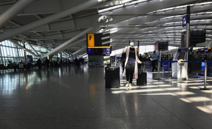 A woman wears a mask as she walks through a quieter than usual Heathrow Airport Terminal 5, in London.