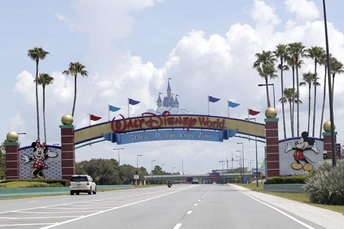 In this Thursday, July 2, 2020, file photo, cars drive under a sign greeting visitors near the entrance to Walt Disney World, in Lake Buena Vista, Fla.