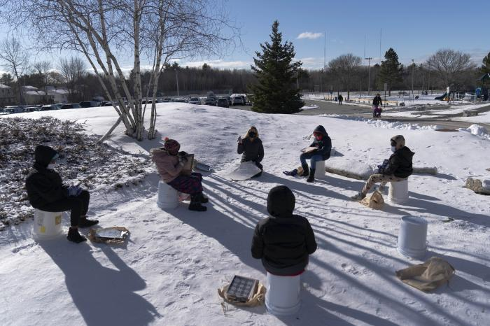 In this Monday, Dec. 8, 2020 photo, a fourth grade class uses upside-down buckets for seats as they study outside at the Gerald Talbot School, in Portland, Maine.