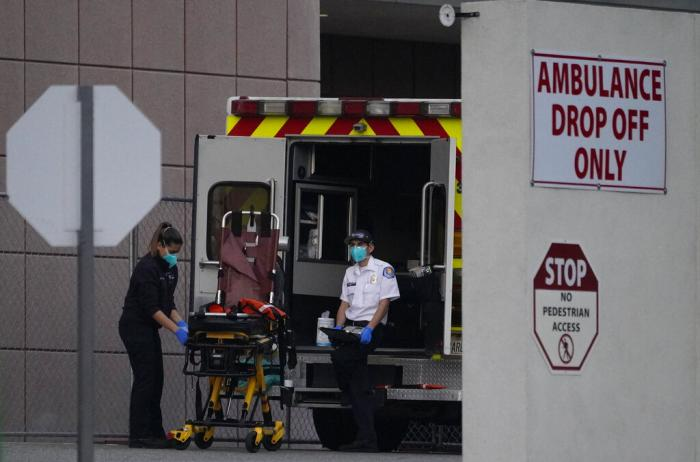 Emergency medical technicians sanitize an ambulance strecher after transporting a patient at Los Angeles County + USC Medical Center in Los Angeles.