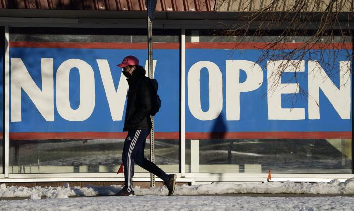 A pedestrian in a face covering walks past the sign plastered on the windows of a restaurant to announce that it is open after closure because of the coronavirus in Boulder, Colo.
