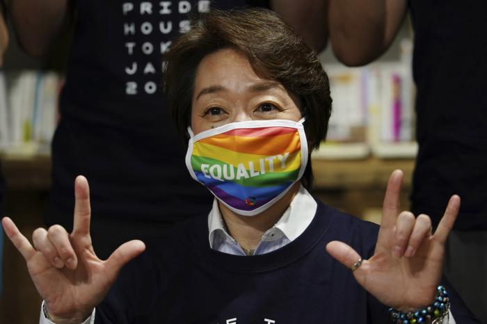 """Tokyo 2020 Organizing Committee President Seiko Hashimoto wearing a rainbow-colored mask with word """"Equality"""" poses for a photo with representatives and staff at Pride House Tokyo Legacy during her visit, in Tokyo."""