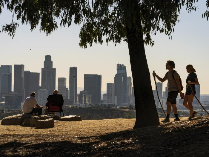 In this Monday, Jan. 11, 2021, file photo, people overlook the skyline of Los Angeles.