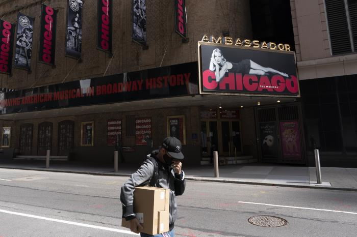 A man walks by the Ambassador Theatre where Chicago last played a year ago, Thursday, May 6, 2021, in New York. Gov.
