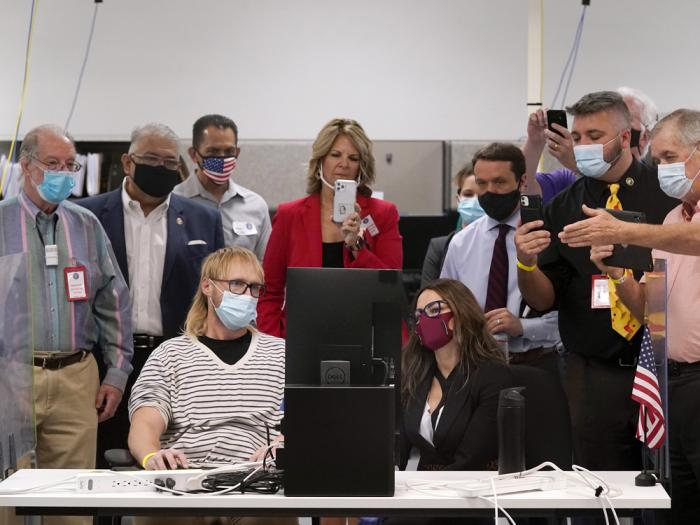 In this Wednesday, Nov. 18, 2020 file photo, Arizona election staff, other state officials and election observers from the political parties, including Dr. Kelli Ward, top middle, chair of the Arizona Republican Party, and Steven Slugocki, far right, chair of the Maricopa County Democratic Party, participate in a ballot adjudication test on a computer screen as the Maricopa County Elections Department conducts a post-election logic and accuracy test for the general election in Phoenix